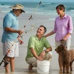 A Couple with their dog talking to a fisherman at the beach