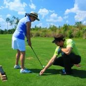 Pro helping a lady with her swing