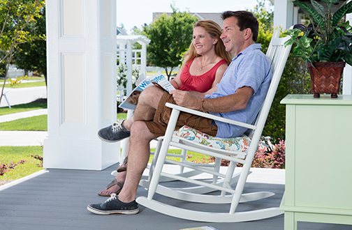 Couple Enjoying a Beautiful Day in Brunswick Forest, Sitting in Their Rocking Chairs on the Front Porch